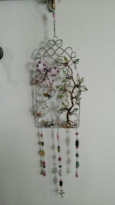 Wire wrapped beaded sun catcher with swivel so it can spin in the breeze. Butterfly and spider, snail and bumblebee with vine on a trellis.