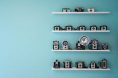 love both the tiffany blue walls and the neat shelf organization of a fab camera collection.