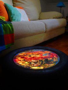 Mesa de apoio da sala feita por Ana Cristina Raposo. Foi executada com um pneu, um vidro do diâmetro do pneu, desperdício de mecânico e uma lâmpada no interior, simples! Poderá ser colocado na parede e funcionará como candeeiro de presença.