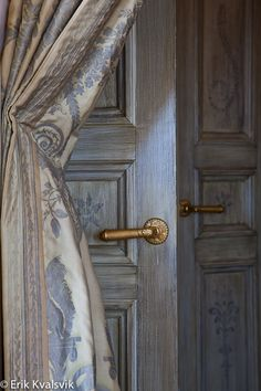 I love the look of these blue and cream drapes highlighting the door and speaking of the door, look at it closely, pickled with stenciled detail is quite attractive.
