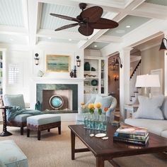 Pale blue beadboard ceiling, wicker ceiling fan, white walls, pale blue furniture, wood accents.  Yum-may.