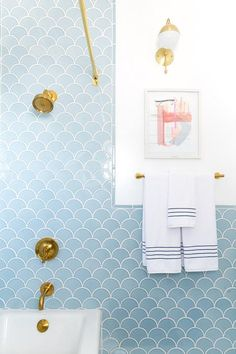 Blue and gold bathroom boasts a drop in tub accented with blue fan tiles, Fireclay Ogee Drop Tiles, lined with an antique brass shower rail as well as a Kohler shower kit in brushed gold.