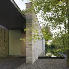 A shallow pool of water wraps around the grey brick facade of this house in Goirle, the Netherlands