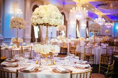 Adam Leffel Productions Reception Decor. This unique and elegant gold candelabra features a large lush arrangement of white hydrangea, ivory spray roses, as well as vendela and quicksand roses. There are four smaller flower clusters of the same flowers atop the arms of the candelabra. #adamleffelproductions #wedding #reception #hydrangea #roses #ivory #white #flowers