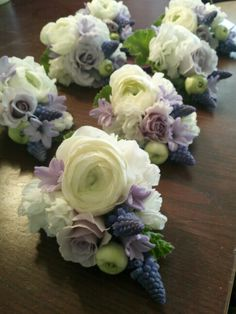 Pretty lavender and white wrist corsages with ranunculs, spray roses,and grape hyacinths