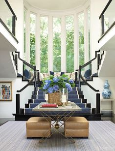 A bold striped staircase runner is tempered by natural-toned entry furniture.