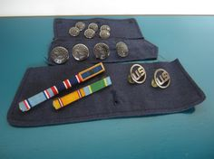 A 14 piece collection of air force buttons and ribbons including:  two ribbon buttons: ~Larger one has Presidential Unit Citation, Air force outstanding unit award, and air force good conduct metal. (4 1/4 inches long) ~Smaller one has a small arms expert marksman and an active duty service ribbon. (2 3/4 inches long)  ~6 small air force cuff buttons made by waterbury button co (1/2 inch) ~4 large air force coat buttons made by waterbury button co (3/4 inch) ~2 U.S. buttons (1 inch)