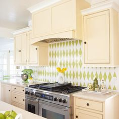 Golden yellow cabinets let a chartreuse-and-white harlequin-pattern tile backsplash dominate the view in this sunny #kitchen. Beige solid-surfacing countertops add a subtle presence.
