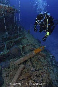 Scuba diver looks at live 5 inch shells on submarine wreck USS Apogon, Bikini Atoll, Marshall Islands, Micronesia, Pacific