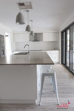 Red Lily Renovations - Perth. White kitchen with Caesarstone benchtop. Tadao 1 Flat Top Pendant in Concrete from Beacon Lighting. Walk in pantry. Splashback from Ceramo Tiles