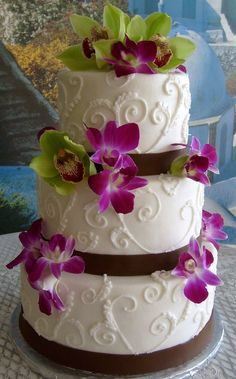 Vanilla cake with chocolate mousse filling, covered with buttercream and brown ribbon made with fondant and real orchids.