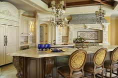 Ornate details abound in this Old World kitchen, including the metallic range hood. The reclaimed tin hood shell features scrollwork similar to the moldings throughout the space.