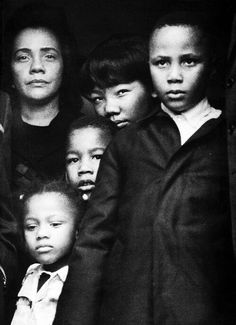 Coretta Scott King (with her 4 Children) are watching from a Doorway as Dr Martin Luther King's body is being removed from the plane after landing at Hartsfield Airport in Atlanta on the return from Memphis.  Photo by Harry Benson