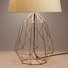 Crafted in India with a light, open design in rich pewter, our exclusive table lamp is an architectural statement piece with an intricate geometric construction.