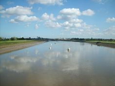 Standing on a bridge looking downstream towards the town of King's Lynn, Norfolk, England.  The river is high, and is remarkably ripple free, allowing the reflected clouds to seem to drift in the water, as well as the sky.
