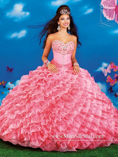 Pink organza quinceanera princess ball gown with a sweetheart neckline, beaded upper bodice, ruching from bustline to waist, skirt with diagonal ruffles, lace-up back, detachable spaghetti straps, and a ruffle edged bolero.