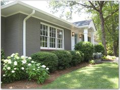 Captivating Gray Brick Ranch Houses Exterior Wall With White Glass Window And White Pipe Drains Also Green Plants And White Flowers In The Front Yard As Well As Ranch House Remodels Plus Landscaping Design, Wonderful Design For Ranch House Curb Appeal: Exterior