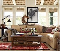 A perfect balance of rugged and refined, this living space is imbued with style and spirit. An overstuffed, spacious couch sets a casual tone and encourages family and friends to gather together. A wood horse sculpture, charcoal saddle art and Kilim throw pillows make for bold design strokes that give the room its distinct western style. Pulley lighting and salvage style tables nod at a romantic, rugged past.