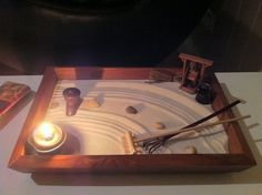 This is a homemade miniature Zen Garden made from a picture frame, some sand and round aquarium river stones and a candle. A bamboo back scratcher as a rake and voila! A Zen Garden for your bedroom or dorm room. You can get even fancier by buying a small Bonsai tree or one of those battery powered Zen fountains at Wal-Mart for $10.00 and add the soothing sound of trickling water to your garden. Sam.