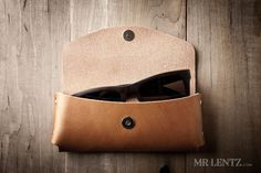 Help protect your sunglasses with the Mr. Lentz Leather Sunglasses Case. An original design built with durable thick full-grain, vegetable-tanned leather sourced from the top tannery in the U.S. The leather sunglasses case is handmade in beautiful detail and secured with the highest quality solid brass rivets a cowboy can find. Designed to fit most sizes of sunglasses, it should fit pairs up to 6 inches wide, 2.5 inches tall, and 1.75 inches deep. Secured with a magnetic snap. Mr. Lentz…