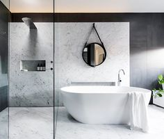 Award winning minimalism by @minosa_design, photography by @nicoleengland.  The designers nailed the client's brief. What was it? Sharp and edgy, monotone colour palette, natural material feature, quality fixtures and more STORAGE.... We love how the client thinks! Simply FEARLESS. All that marble ✔️, black details ✔️and of course a @gubiofficial mirror. Tick tick tick.  Happy Day friends.  #minimalism #minimalist #marble #marblebathroom #monochrome #monochromehome