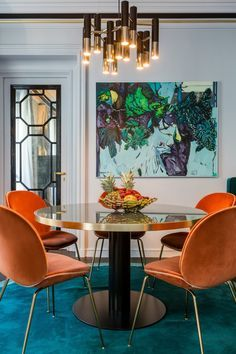 Gerard Faivre, gerardfaivreparis.com | luxury apt on Rue Bonaparte in Paris, Second Empire colors - oranges, greens, blues and shades of gold, Luxe Dining Room with gold pendant light and orange velvet dining chairs
