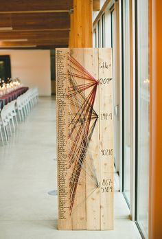 Brides.com: . Color coordinated strings guide guests to one of four tables on this DIY seating chart.