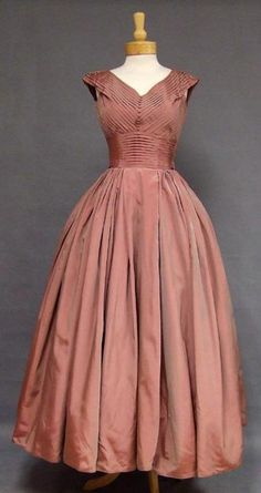 A gorgeous Fred Perlberg evening gown in a lovely iridescent dusty rose taffeta. Fitted, finely pleated sleeveless bodice with a row of small self fabric buttons. Dress has a full, gathered skirt (shown here with an additional crinoline... not included). Side metal zipper.
