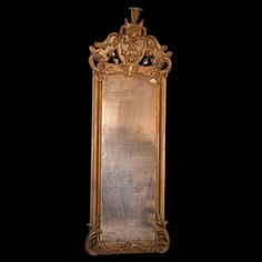 Lot #122: Gilt Wooden Mirror  DESCRIPTION: Antique hand carved gilded wood mirror. Features a patinated mirror, encased by a gilt wooden frame. Frame is topped by a plague with the visage of the God of Mercury wearing a winged helmet surrounded by vinal floral motif encompassing the length of the frame.  CIRCA:19th Ct. ORIGIN:Italy DIMENSIONS:H:98″ L:31″