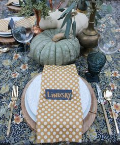 The Perfect Thanksgiving Table: floral printed tablecloth, polka dot napkins, brass silverware, shades of green and white heirloom pumpkins #thanksgiving #fall #table