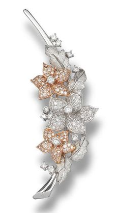 Brooch designed as a floral spray, pavé-set with brilliant-cut diamonds, highlighted throughout with similarly-cut diamonds, to stylised matt leaves, mounted in 18k white and rose gold