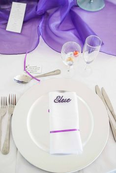 Monte Vista Venue purple table placing with a purple laser cut name, purple ribbon around the napkin and two lindt chocolate balls as thank you gifts