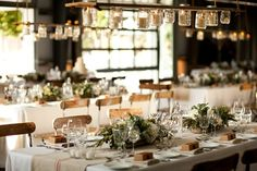 déco mariage champêtre sur la table avec nappe blanche, arrangements floraux et lustre linéaire DIY en bocaux