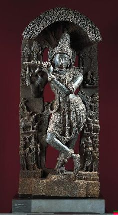 Krishna Fluting in Brindavan, Karnataka, 1100-1150 63 x 26 in.  The monumentality and deep carving of this piece make it one of the finest examples of the ornate style that developed during the Hoysala Dynasty (early 12th to mid-14th century). Krishna spent his early life fluting in the bucolic groves at Brindavan while tending to the animals and the young ladies. Adorned with gems and jewels, he is accompanied by his wives, other musicians, and admiring sages.