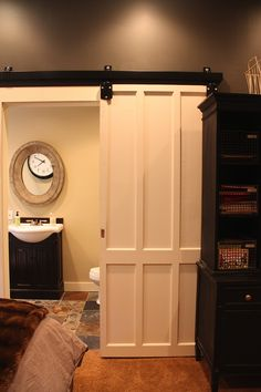 sliding barn door - bought the track at a local hardware store and sprayed it black, found the door at a salvage yard for $30! I need to copy this!!!