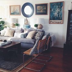 Layering  rugs can add depth and coziness to a space such as this living room. Combined with vintage chairs and a plush sofa, this room has major understated style. From Amen Inspired Design.
