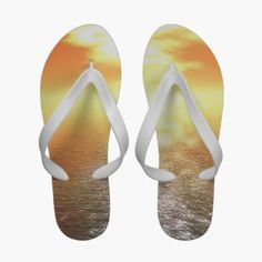 Beach Sandals with Orange Sunset Over Sea Horizon. The sun sets behind golden orange clouds and over a calm sea with haze on the horizon on these beach themed flip flop sandals.