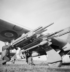 Armourers fit two extra 60-lb rocket-projectiles to the four normally carried on the wing rails of Hawker Typhoon Mark IB, MN178 'PR-V', of No. 609 Squadron RAF at B77/Gilze-Rijen, The Netherlands. The ability of the Typhoon to carry  twelve instead of eight RPs was, however, little-used.