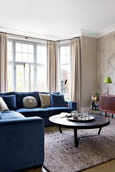 Living Room with Velvet L-Shaped Sofa and Map Print Wallpaper in Living Room Design Ideas. Glamorous modern and neutral living room blue velvet sofa, drinks trolley and thick grey rug.