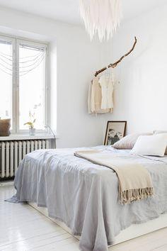 Sängyn päällä oleva kevyt peitto on ommeltu kahdesta pellavaisesta pöytäliinasta. Myös pellavatyynyt on ommeltu itse. Emmi ei halunnut ikkunaan verhoja vaan teki niiden tilalle herkän koristeen puuhelmistä. Sängyn vieressä lattialla oleva grafiikantyö on peräisin Emmin mummolta. Katossa riippuva paperivalaisin sekä ikkunalaudalla oleva bambulankakori ovat niin ikään Emmin tekemiä.