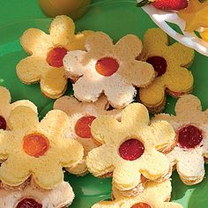PB & J Blossom Sandwiches: use cookie cutter for flower then with water bottle cap in 1 of the 2  flowers use cap to make hole in middle. On whole flower w/o hole spread PB the top layer jelly. Put slice with hole on top do jelly shows through hole