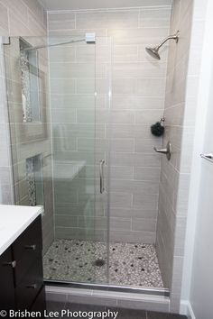 Frameless sliding glass door with light grey horizontal tiles accented with marble pebbles. There are two nooks in the shower wall. Gray Shower Tile, Bathroom Shower Doors, Frameless Shower Doors, Small Bathroom, Frameless Sliding Shower Doors, Small Tiled Shower Stall, Walk In Shower Doors, Small Shower Stalls, Master Shower Tile