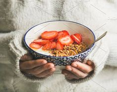 #Healthy breakfast yogurt & granola  Healthy breakfast greek yogurt granola and strawberry bowl in hands of woman wearing white loose woolen sweater selective focus. Clean eating healthy vegetarian dieting food concept