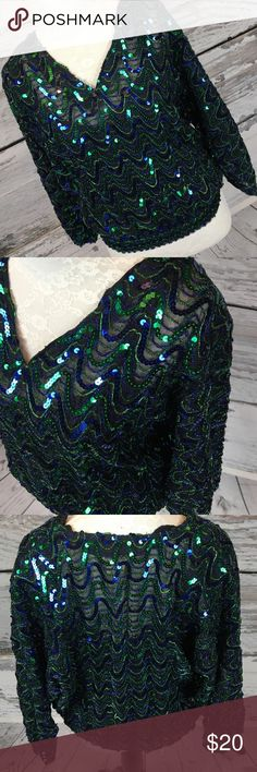 """Golden Girls? Vintage Sequin Beauty Look at this GEM!!! Vintage sequined blinged out beauty!!! Complete with shoulder pads!!! Made in the USA by Flagg Petites. Dolman style 3/4 sleeves, stretchy, attached black tank. Black with green & royal blue sequined & glittered yarn. It has a very small pull in the yarn in a spot or 2 but overall LOVELY condition!! Fits my size 2/4 mannequin perfectly!!  Measurements (flat): Armpit to armpit: 25"""" Armpit to cuff: 15"""" Shoulder to bottom: 23"""" Across…"""