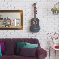 boa ideia para economizar espaço: se você ama música e curte tocar violão, por que não fazer desse hobby parte da decoração??? adoramos o ar despojado de um instrumento pendurado... (e de quebra te poupa um canto do armário) ♥ #todacasatemumahistoria #tijolinho #violão #decoração
