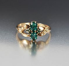 Two oval faceted emeralds flanked on each side with two cabochons and accented with delicate pearls comprise this antique Victorian ring. Crafted in a warm 10K yellow gold, the emeralds are all prong