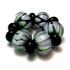 Glass Lampwork Beads Green Black Purple Carnival Glass Harlequin Beads. $37.00, via Etsy. Great gift for the jewelry maker in your life!