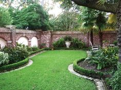 A clipped edge of boxwood frames the garden beds and lawn in this brick walled landscape.