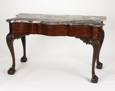 Slab Table, 1765-1775, Unknown maker, American, Philadelphia, Pennsylvania -   Mahogany, pine & marble, 32 x 54 x 26 3/4 inches - Beautifully carved, this table exhibits the opulent rococo style fashionable in Philadelphia at the time of the American Revolution. An unknown master woodcarver completed the delicate acanthus-leaf ornament & the ball-and-claw feet on this pier table, while a skilled cabinetmaker completed the veneered frame.