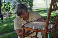 Lori Burris demonstrates her technique in fixing broken rattan and wicker chairs during the Friday market